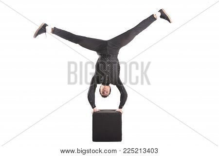 Guy performs stand upside down on the black cube isolated on white background for any purpose
