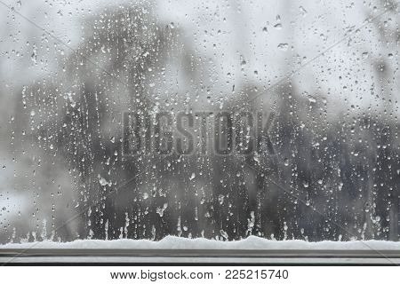 snow and rain drops on a window, bad weather background with copy space