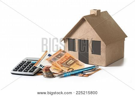 money and calculator in front of a house model from cardboard, financial planning  for property investment or rental costs for a home, isolated with shadows on a white background