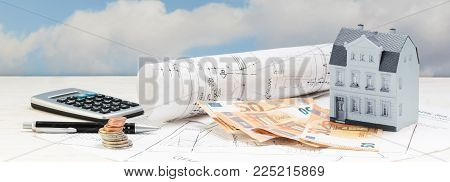 investment in old building renovation, model house, money and calculator on architectural plans, real estate concept in panoramic banner format, copy space, selected focus