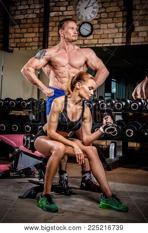 Sports couple is working out at gym. Fitness woman doing exercising with dumbbells and Muscular macho man showing muscles straining.
