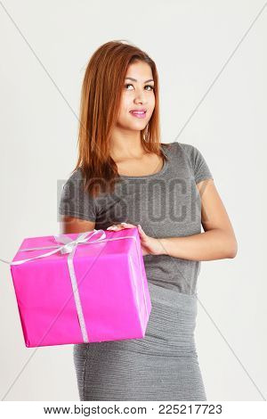 Occasions gifts people concept. Beautiful woman with pink gift. Young blonde lady wearing nice gray outfit, top and skirt.  Girl is mixed race.