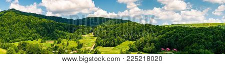 panorama of mountainous rural area in summer. beautiful landscape of the forested hill and village in the valley. agricultural fields on grassy slopes under the cloudy sky
