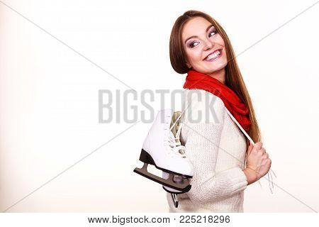 Woman with ice skates getting ready for ice skating, winter sport activity. Smiling cheerful girl wearing warm clothing on white