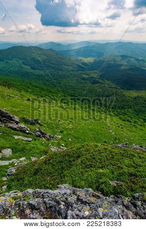 mountain behind the valley viewed from rocky cliff. beautiful summer landscape with grassy slopes under the cloudy sky. location mountain Pikui, TransCarpathia, Ukraine