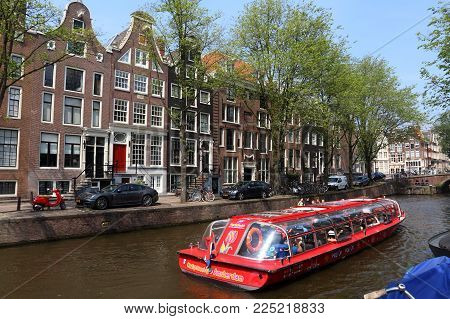 Amsterdam, Netherlands - July 7, 2017: People Ride A City Sightseeing Boat Along Leidsegracht Canal