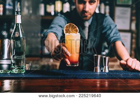 Portrait Of Handsome Bartender Serving Perfect Summer Drink, Chilled Rum With Orange Juice And Tequi