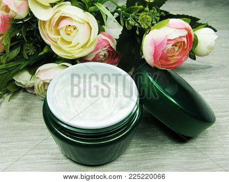 Cosmetic Cream For Skin Care And Rose Flowers On Background