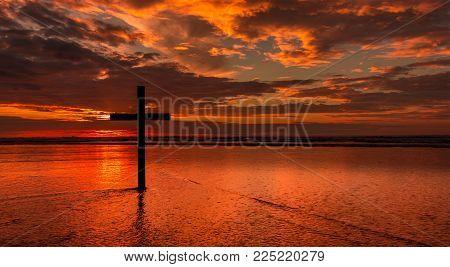 Dark cross on a beach with a red sunset sky.