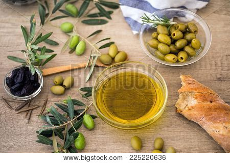 oil olive-green olive with ciabatta bread and black olive over of wooden table background