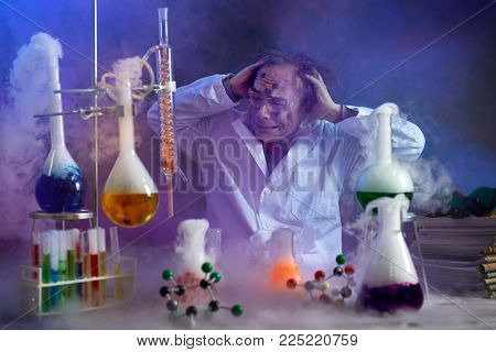 Disappointed chemist looking in his failed experiment in smoke of explosion