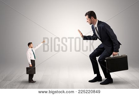 Small businessman in shirt pointing to an afraid businessman
