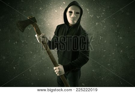 Masked armed villain in empty dark room with gun axe chainsaw mallet wrench