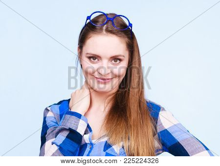 Studying, beauty of education and fun concept. Attractive nerdy woman in weird big glasses on head. Studio shot on blue background