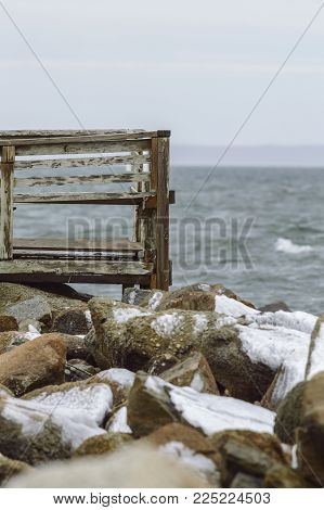 Dilapidated deck overlooking Buzzards Bay on icy winter day