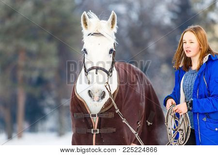Young teenage girl walking with her white horse in winter park