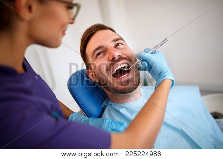 Female dentist with dental mirror checking up male patientâ??s teeth