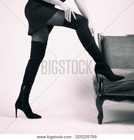 Girl in Hessian boots in high heels in studio.