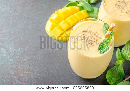 Mango lassi with mint leaves, traditional indian drink in glasses on a black dark stone table. High angle view, horizontal image, copy space