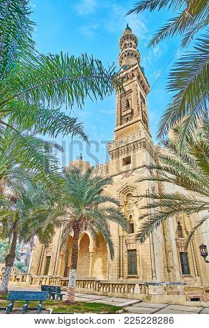 The scenic Abu al-Abbas al-Mursi Mosque with tall minaret and carved patterns is seen through the lush palm trees of the garden, Alexandria, Egypt