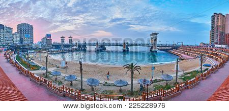 ALEXANDRIA, EGYPT - DECEMBER 17, 2017: Romantic sunset in coastal Stanley neighborhood with a view on the same named sand beach and scenic bridge with towers, on December 17 in Alexandria.