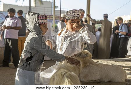 Nizwa, Oman, Febrary 2nd, 2018: Omani Boys At A Traditional Goat Auction, Resting And Keeping An Eye