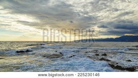 Stormy blue Ligurian sea with white spumy waves crashing against brown rocks. During dawn in summer. Crete, Greece