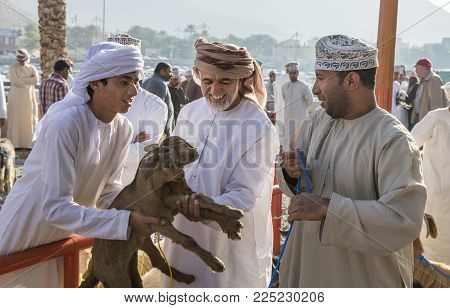 Nizwa, Oman, Febrary 2nd, 2018: Omani Men Evaluating A Baby Goat  At A Traditional Goat Auction