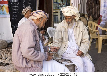 Nizwa, Oman, Febrary 2nd, 2018: Old Omani Men Checking Out Knives At A Weapons Market