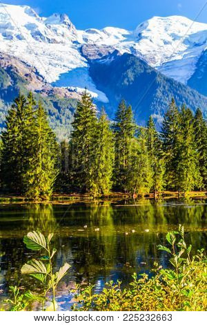 The lake reflected the evergreen spruce and snow-capped Alps. The mountain resort of Chamonix, Haute-Savoie. Concept of active and ecological tourism. City - Park is illuminated by the sunset