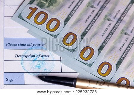 Gold fountain pen lies on the asset description document. One million dollars out of five hundred dollar bills. Bitcoin Blue stamp on a paper close to the venue for the signature. Concept. Declaration