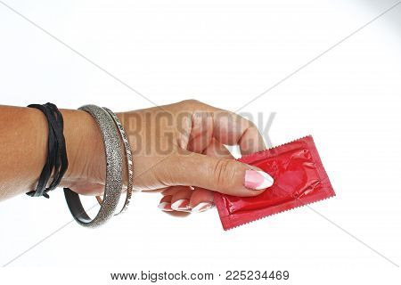 Woman hand holding condom on isolated white cutout background. Studio photo can illustrate hpv std gonorrhea, chlamydia, trichomoniasis, hepatitis B, and AIDS.