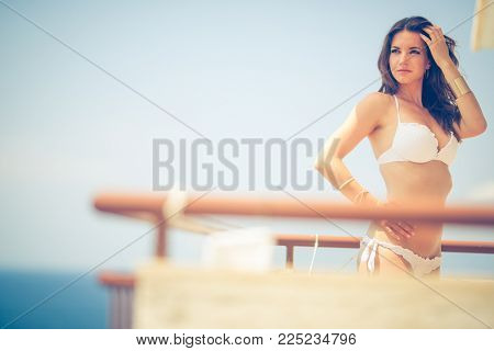 Beauty, spa and resort concept - beautiful, young woman by the sea on a balcony of a resort/hotel room