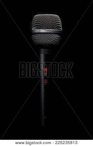 Black classic microphone on black dark background .