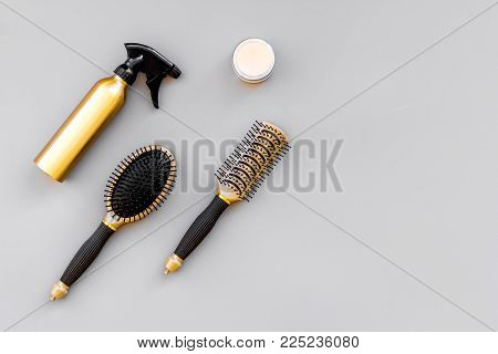 Professional hairdressing tools in beauty saloon. Combs, spray on grey background top view.