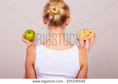 Woman back view holds in hand cake sweet bun and apple fruit choosing, trying to resist temptation, make the right dietary choice. Weight loss diet dilemma concept.