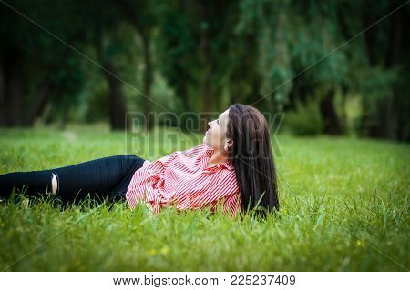 Beautiful young woman lies down on the grass smiling