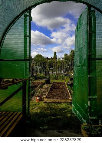 Poly tunnel on an allotment garden in London with blue sky and clouds in the background