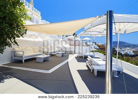 Outdoor white table and sofas on terrace overlooking sea, Oia Village, Santorini, Cyclades, Greece