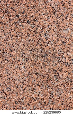 Textured surface of natural red granite tile