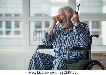 Sad Senior Male Sitting In Wheelchair In Room With Hopeless Face. He Is Holding His Eyeglasses And T