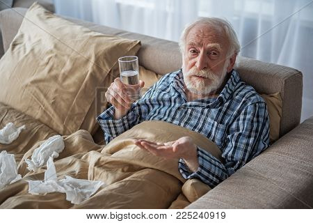 Upset Old Man Looking At Camera With Sad Look. He Is Holding Pills And Glass Of Water And Lying In B