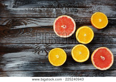 fresh ripe oranges and grapefruits on wooden background