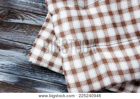 two checkered pillows on brown wooden panel