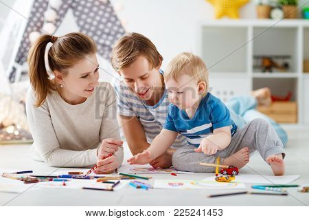 children's creativity. happy family mother father and baby son draw together