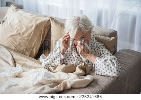 Sick Mature Woman Blowing Her Nose And Holding Her Head With Tired Look. She Is Sitting In Bed Cover