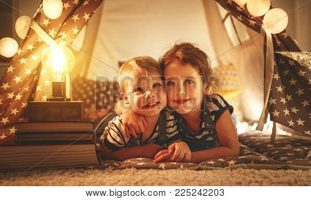 happy family loving children brother and sister play, laugh and hug   in dark tent in playroom at home