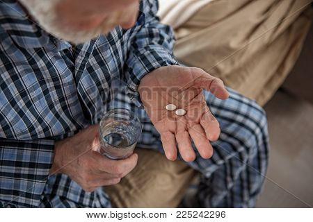 Top View Close Up Of Male Hands Holding Pills And Glass Of Water. Focus On His Hand. Old Man Is Sitt