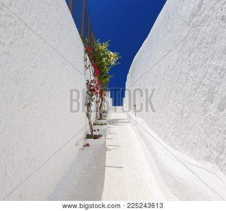 narrow passage between two high white walls with blue sky, bright Sunny day. Santorini, Greece