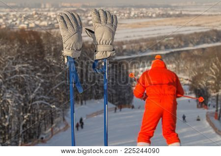 Ski gloves on the ski poles, and a silhouette of skier, skiing down the hill, Moscow region .